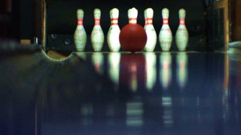 Bowling.  Ball knocks down skittles. Strike.