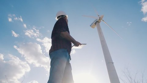 engineer at windmill power plant with tablet in hand on sky background