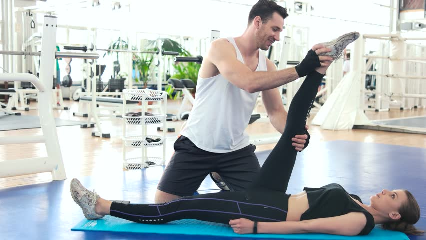Fitness trainer stretching leg of young woman. Male fitness instructor helping to female client stretching leg. Developing flexibility of body.