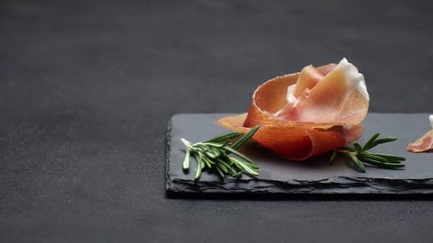 sliced prosciutto or jamon meat on dark concrete background