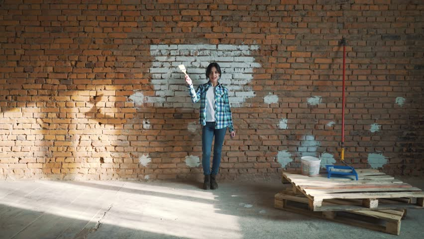 girl Builder on brick wall background dancing and paints the wall with white paint #1010937182