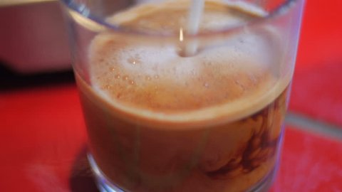 Adding frothy milk to a cup of espresso or latte in a clear glass - close up