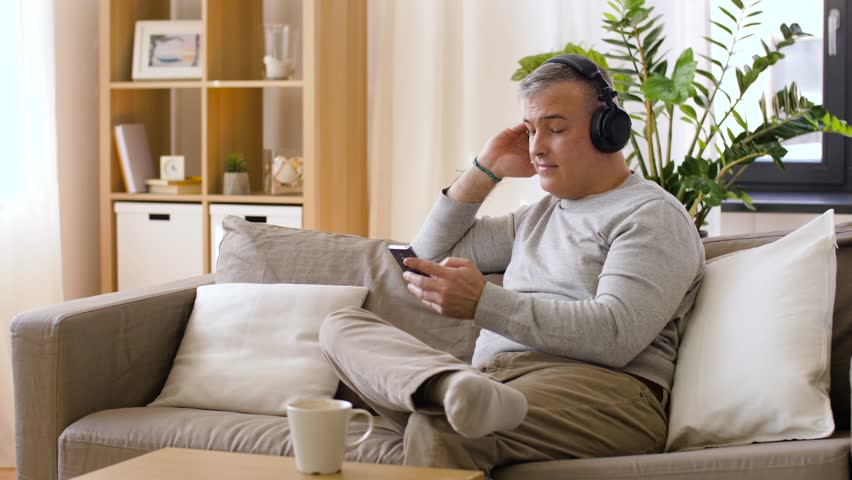 Happy man with smartphone and headphones listening to music at home | Shutterstock HD Video #1010982032