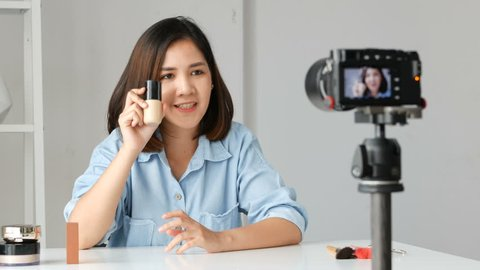Young asian woman  influencer beauty fashion blogger recording video Presen her product. shooting on camera.