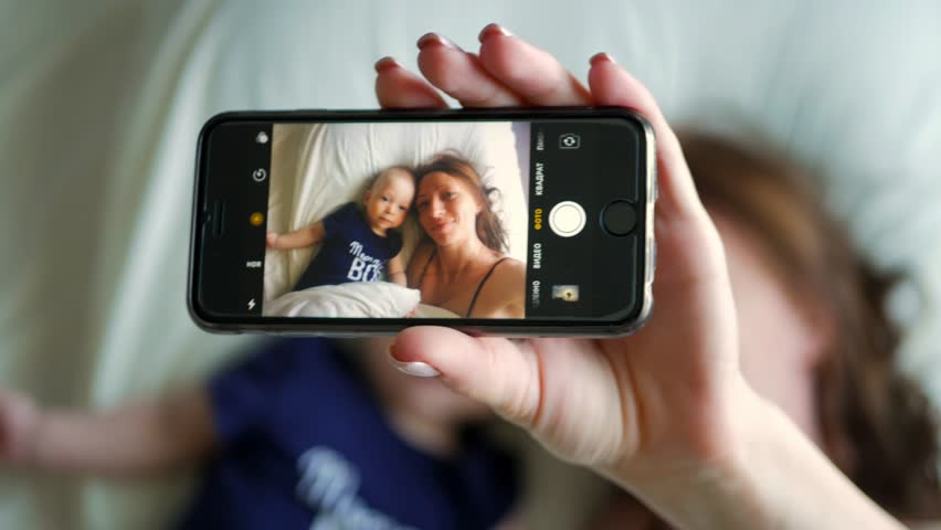 Mother and small baby boy doing selfie on bed. Resting in bed together. Maternity concept. Parenthood. Motherhood Beautiful Happy Family Stock Video Footage.