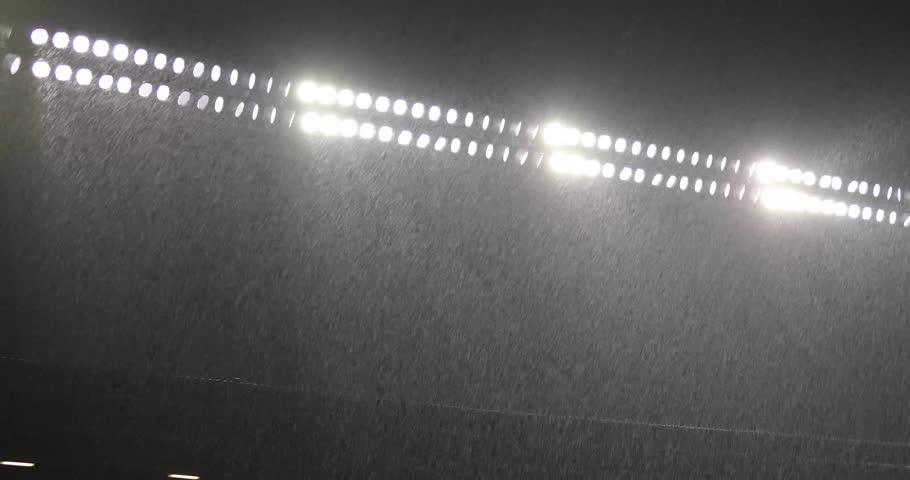 Heavy rain under lights of baseball stadium.