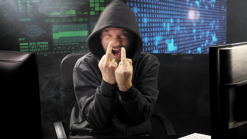 Angry hacker showing middle finger looking camera