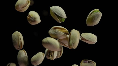 Pistachios bouncing against to the camera on a black background in slow motion closeup,