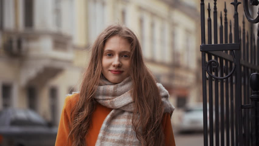 Portrait of elegant european woman 20s wearing coat and scarf laughing at camera and expressing joy, while strolling through city street. Film look | Shutterstock HD Video #1011089492