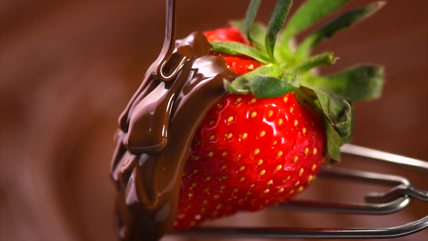 Strawberry in chocolate over swirl brown background. Melted Chocolate pouring on fresh ripe juicy strawberry close up. Dessert. Gourmet food. Fondue. 4K UHD slow motion video