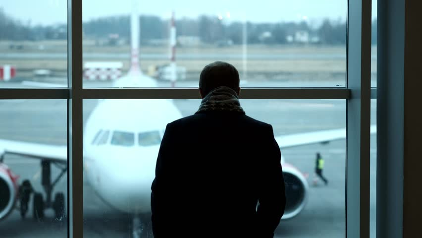 Old Man stand at full height, gaze out airport terminal window, silhouette view. Looks at the plane at the airport   Shutterstock HD Video #1011120122