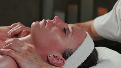 Hands of professional masseuse massaging woman's face in beauty saloon. Attractive enjoying female at spa health club getting facial massage. Skin care, wellness concept.