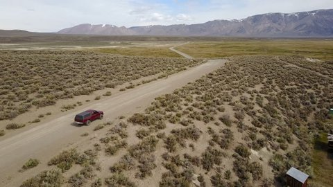 Aerial drone follow shot of a German Shepard dog running in front of a pickup truck in a vast desert countryside on an endless rural dirt road with snow-capped mountains in the distant background.