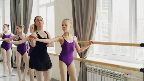 Diligent young ballet-dancers are doing plie and battement tendu while their female teacher is correcting wrong positions and giving instructions.