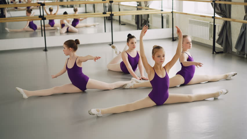 Young diligent ballet students are doing leg splits and bends during classical ballet class. Flexible girls are wearing beautiful bodysuits and pointe-shoes.