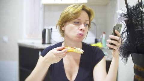woman is eating pizza in the kitchen at home and using her smartphone, 4k, background blur