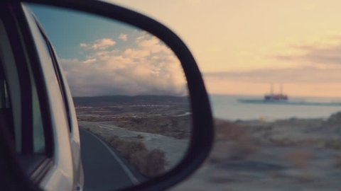 view in the rear view mirror while driving a car romance of long-distance travel