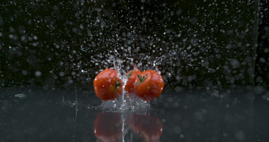 Three tomatoes falling and splashing in slow motion. Food cinematic scene. Shot with Phantom Flex.
