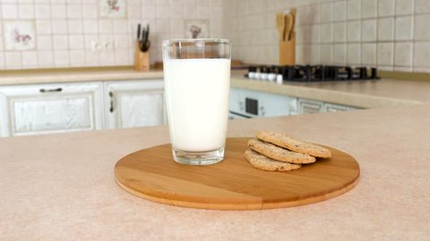 Close up of a glass of milk with healthy crunchy breakfast biscuits. Rotating camera with white kitchen on the background. Dolly-shot.