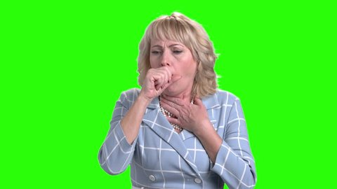 Mature woman is coughing on green screen. Middle-aged woman having cough on chroma key background. Dry cough concept.