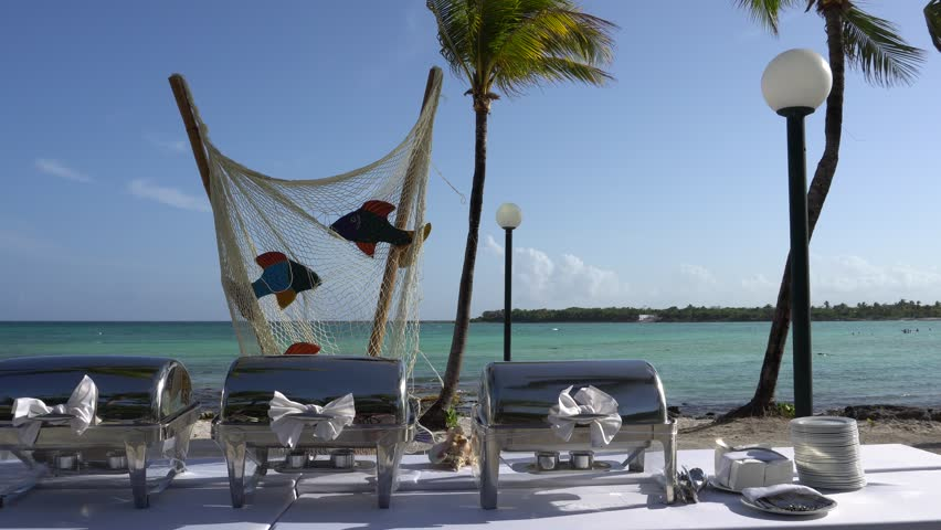 View at luxury resort hotel beach of tropical coast. Leaves of coconut palms fluttering in wind against blue sky. Preparation for Gala dinner. Turquoise water of Caribbean Sea Riviera Maya Mexico.