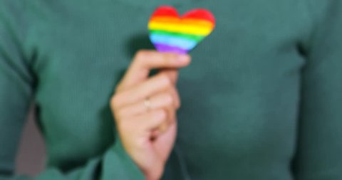 Closeup of a woman hand holding a LGBT flag rainbow heart shape in the studio, shot in 4k resolution