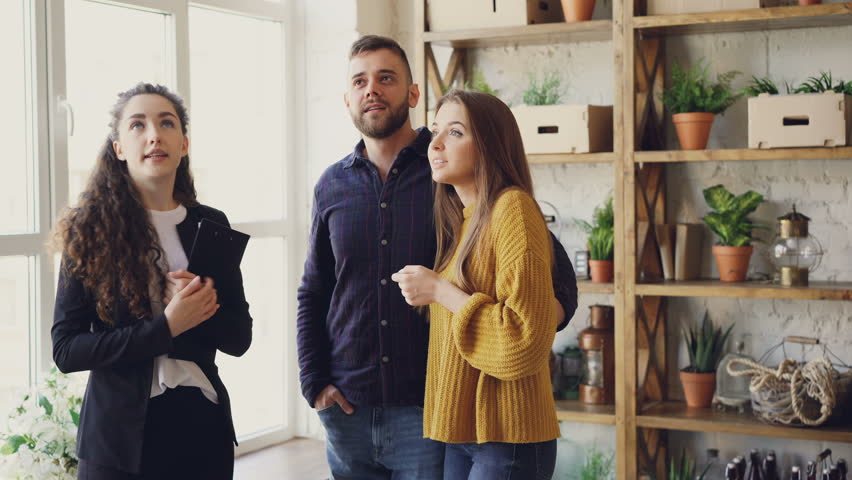 Confident realtor is describing advantages of house to young couple looking around, talking and smiling. Husband and wife are excited about new accommodation.