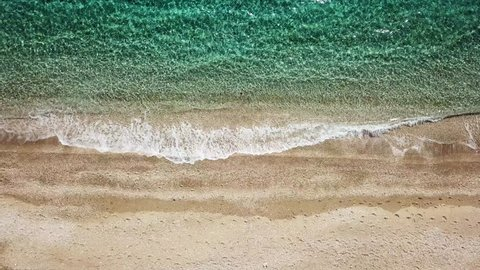 Aerial drone bird's eye view video of iconic beach with turquoise clear waters located in Greek island