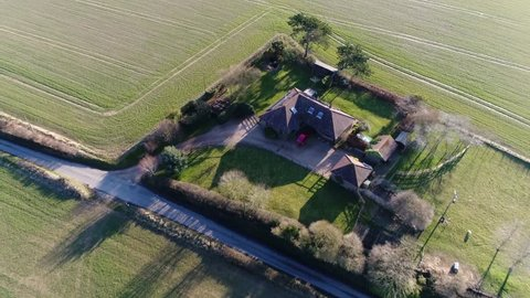 Aerial footage residential real estate panning down showing the single-family detached house property beautiful rural environment green field surrounding the property footage shot during summer day