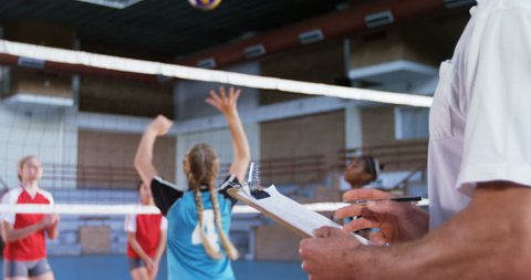 Coach assisting female player in playing volleyball in the court 4k