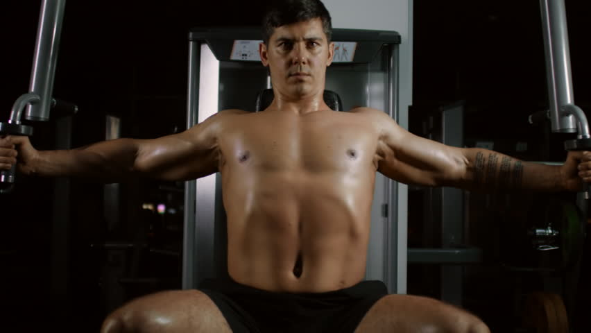 Muscular handsome man doing pec deck butterflies and looking at camera while exercising on fitness machine in gym