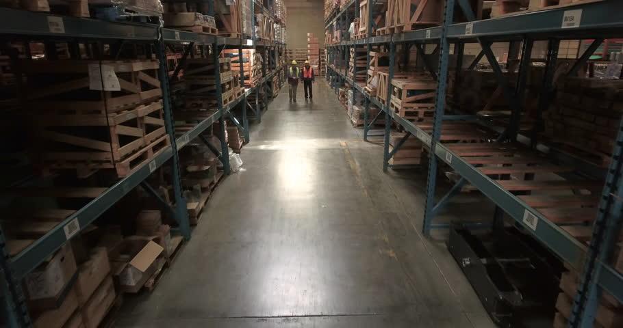Push-in shot of warehouse workers talking | Shutterstock HD Video #1011300362