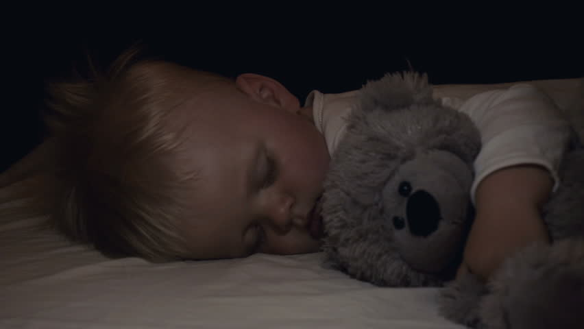 A little boy (son) is sleeping sweetly, blond, mother gently stroking her son, a gray bear toy, in the dark. Concept: children, kids, baby, love, caring family.