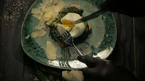 Breakfast. Poached egg, salmon on lettuce on toast bread. On a black wooden background, dolly shot
