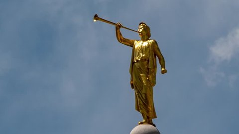 Time lapse cloudscape of Angel Moroni - the Mormon prophet shown as a golden statue on the top of Mormon Temples. Zooming out to reveal a wider scene.
