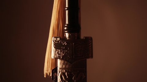 A woman's hand takes a sword out of the sheath, close-up