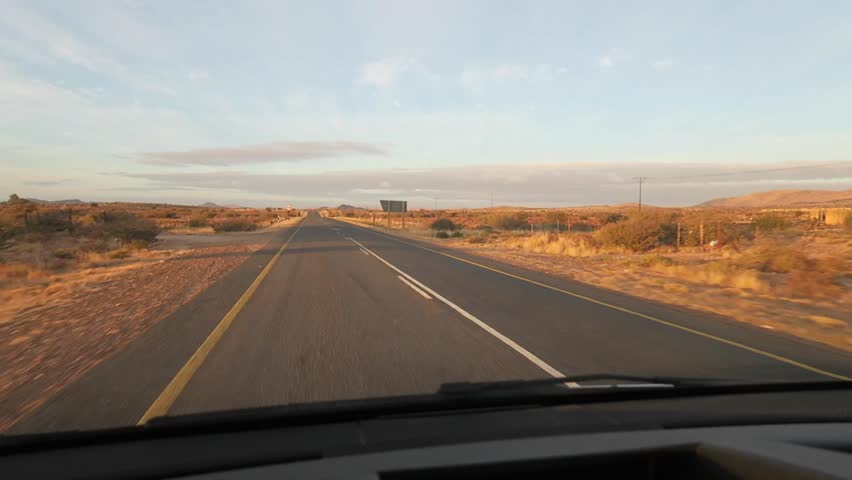 Driving along a tar highway in the Northern Cape of South Africa dashcam point of view towards road in out the front of the car   Shutterstock HD Video #1011316022