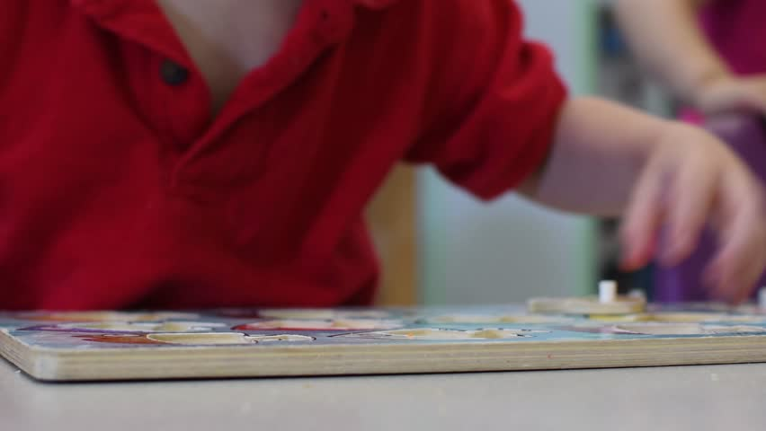 Young child putting together a basic puzzle at a classroom table learning education | Shutterstock HD Video #1011341942