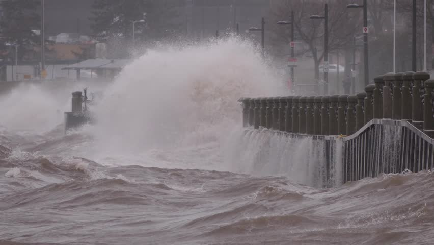 Huge powerful waves breaking at seawall in major severe storm in hurricane force winds   Shutterstock HD Video #1011370562