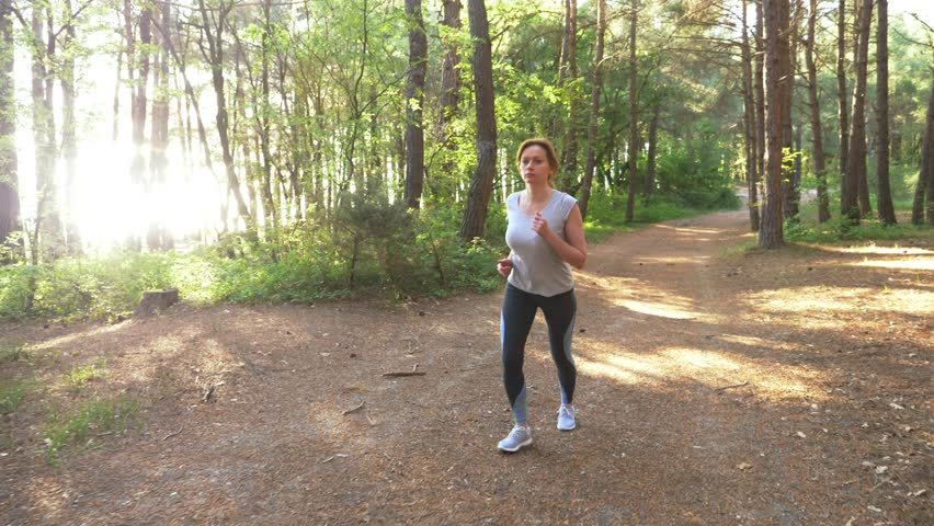 Woman running away on a trail in the sunny summer forest. motivation for sports activity outdoors, training and exercising in beautiful nature. solar glare, slow-motion 4k, steadicam shot #1011380882