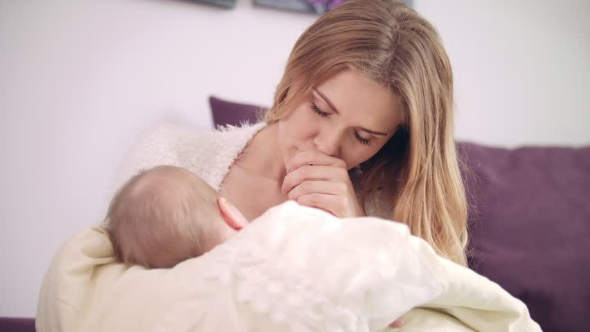 Beautiful woman breast feeding baby. Portrait of mother breastfeeding baby and kissing her. Cheerful mom enjoy breastfeeding. Little baby breast feeding and sleeping. Sweet motherhood