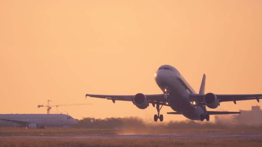 Airplane taking off at sunset. Aircraft takes off at dawn. Long shot