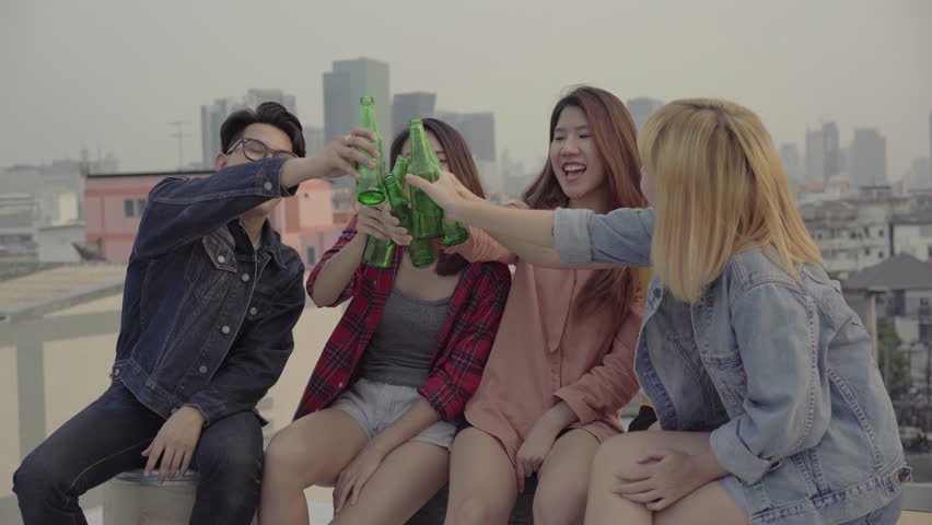 Group of young asian women and man people dancing and raising their arms up in air to the music played by dj at sunset urban party on rooftop. Young asian girls and boy friends hanging out with drinks