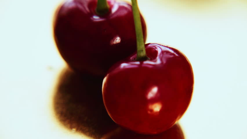 Cherries. Cherry. Red cherry. Two cherries isolated on a golden background. Summer fruits.