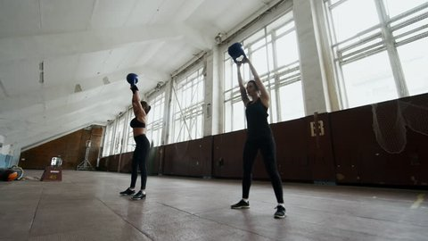 Dolly shot with PAN of strong sportswomen swinging kettlebells in empty gymnasium during cross-training workout