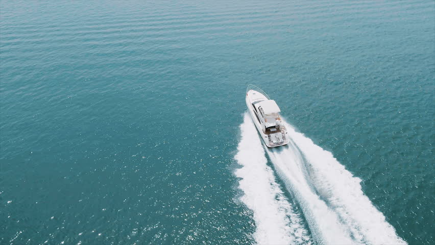 Large white yacht at speed in the Emirates. 4K cinematic video from drone