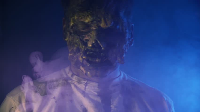 Scary zombie closeup on dark background in Halloween makeup | Shutterstock HD Video #1011440102