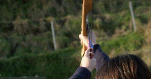 Woman draws an arrow and shoots a bow hitting an arrow target