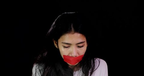 Scared woman with closed mouth using adhesive tape looks sad and crying. Shot in 4k resolution