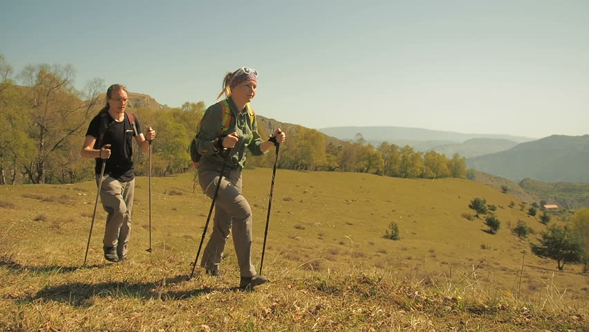Hikers People Hiking Walking With Trekking Poles. Young active man and woman climbing mountain, couple spending summer vacation together. Happy people travelers  travel enjoy view. Hike in mountains.  | Shutterstock HD Video #1011456062